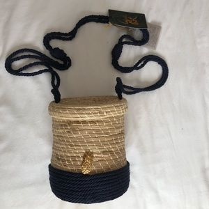 Cylinder straw bag with navy cord details.